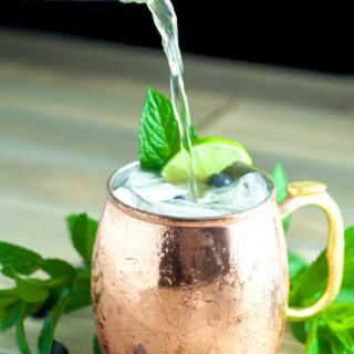 Blueberry Maple Moscow Mule is lightly sweetened with pure maple syrup and muddled fresh blueberries. It is a the perfect light, refreshing summer cocktail! http://www.mamagourmand.com